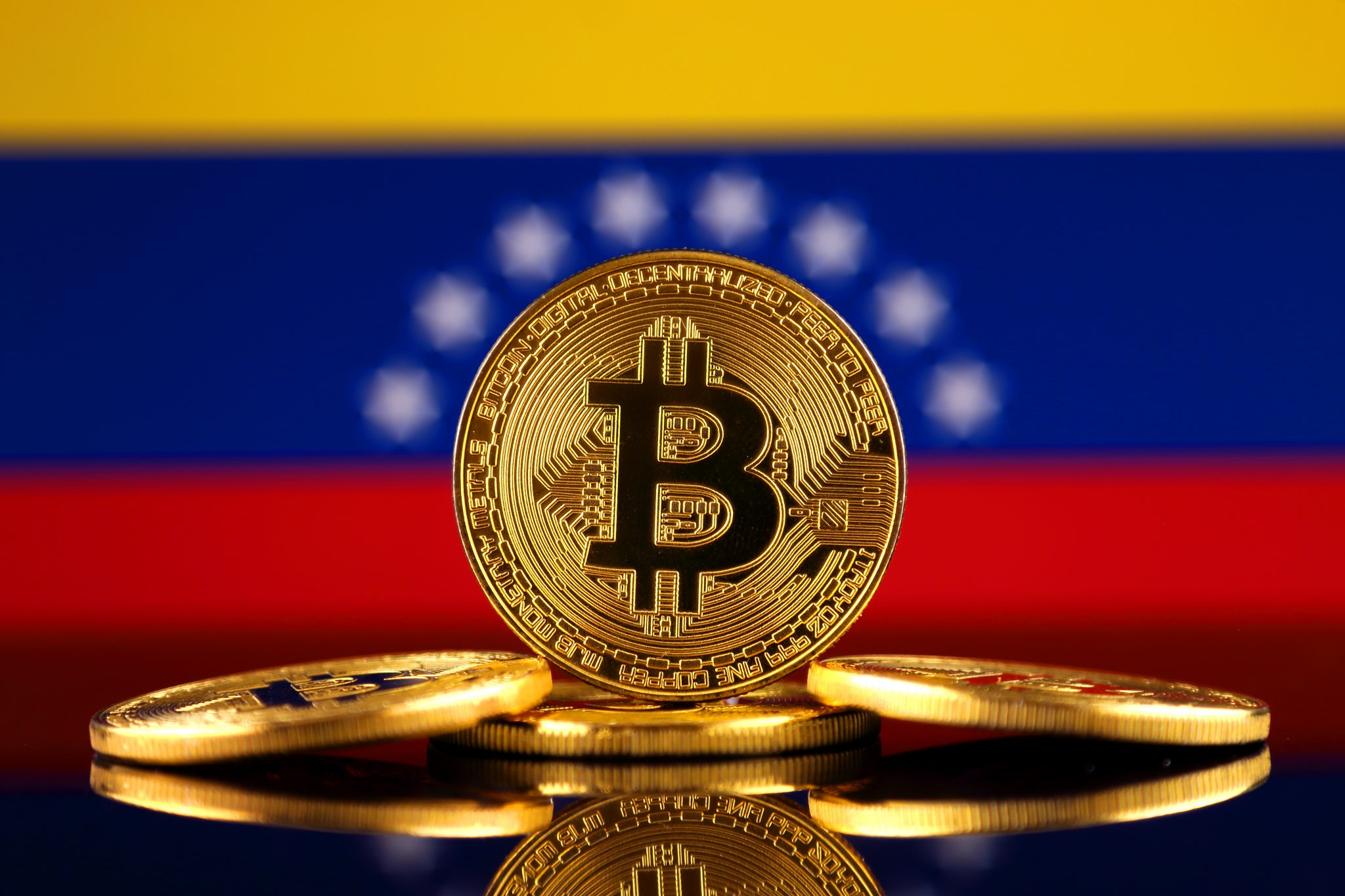 Physical version of Bitcoin (new virtual money) and Venezuela Flag. Conceptual image for investors in cryptocurrency and Blockchain Technology in Venezuela.