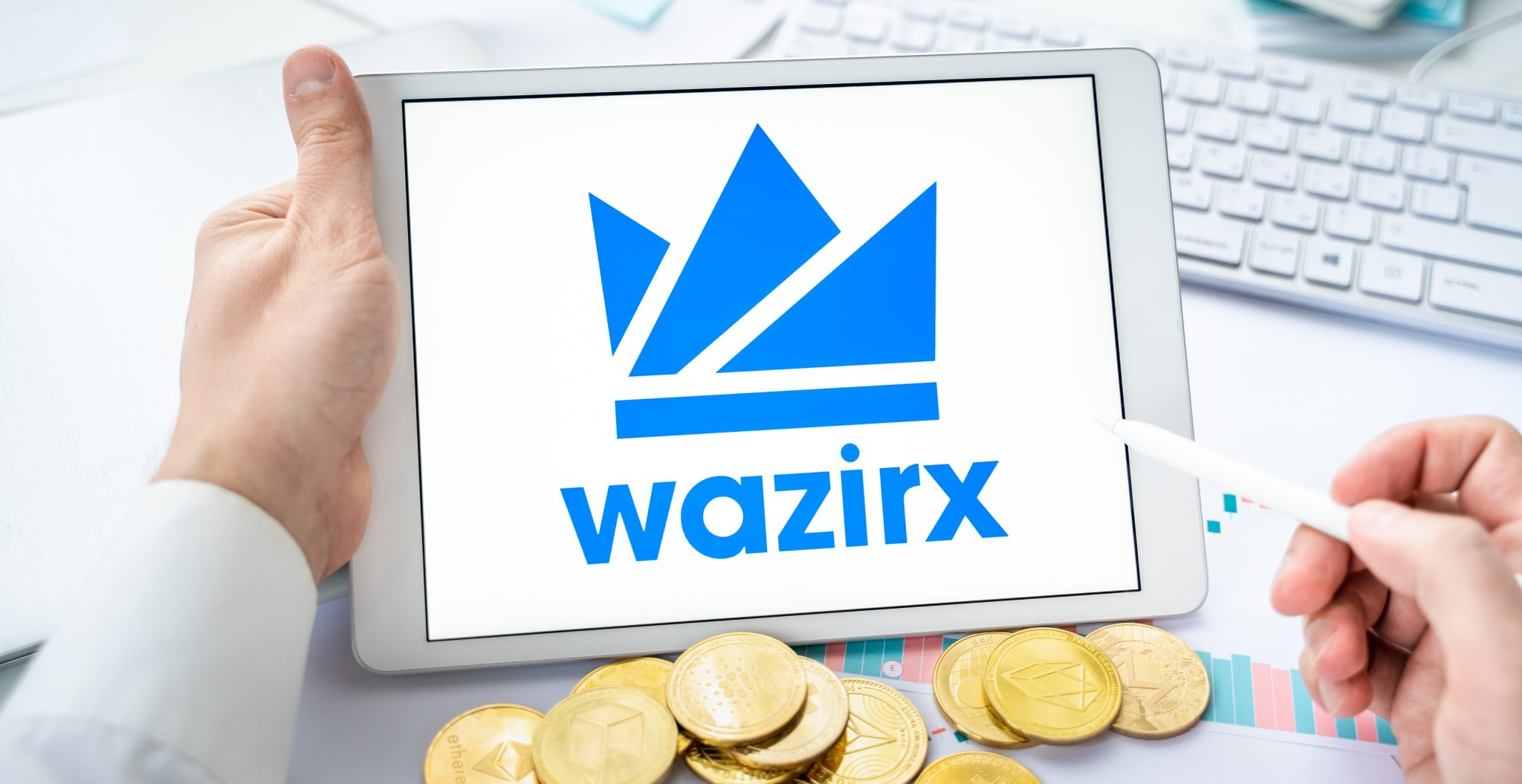 Russia Moscow 06.05.2021.Businessman with tablet.Logo of cryptocurrency stock exchange Wazirx.Trading blockchain platform to buy,sell digital crypto coins,tokens Bitcoin,Ethereum.Business,investing.